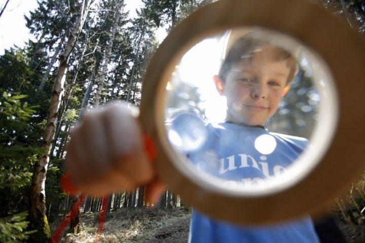 Ein Kind schaut im Wald durch eine Lupe