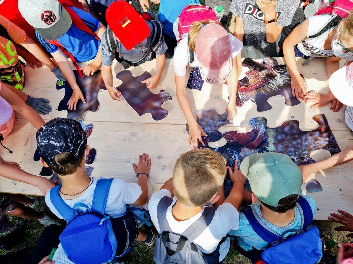 Das Bild zeigt eine Gruppe Kinder, die um einen Tisch mit großen Puzzleteilen herumstehen