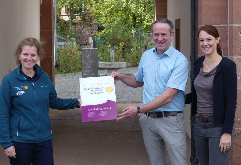 Neuer Partnerbetrieb: Die Direktorin des Biosphärenreservats Pfälzerwald-Nordvogesen, Dr. Friedericke Weber (links), übergibt das Schild an Karsten und Ann-Kathrin Bessai