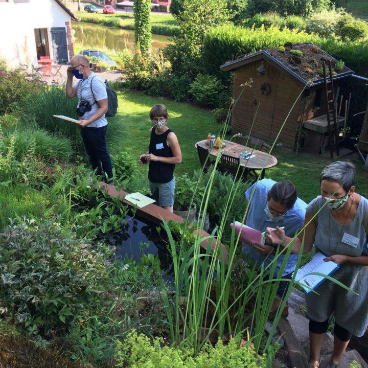 Personen, die zur Jury gehören, begutachten den Garten der Familie Rabel in Volksberg im Elsass