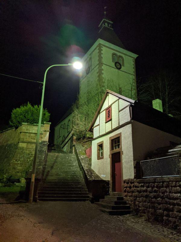 Die Nachtaufnahme zeigt die Straße vor der Rumbacher Kirche im Licht einer sternenfreundlichen Straßenlampe.