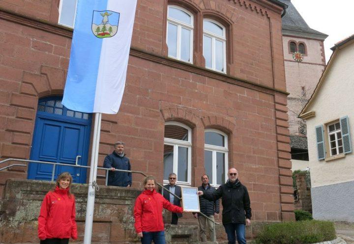 """Mehrere Personen stehen vor dem Rathaus in Rumbach und freuen sich über die Übergabe des Zertifikats """"Gemeinde unter den Sternen"""""""