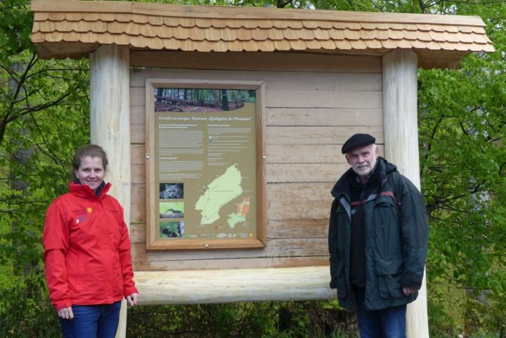 Das Bild zeigt zwei Personen an einem Infoschild über die Kernzonen des Biosphärenreservats Pfälzerwald.