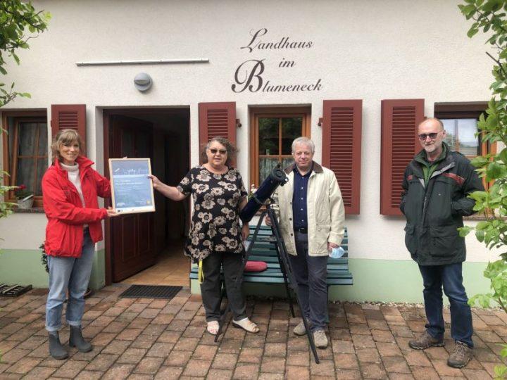 Anna Prim überreicht den Gastgebern vor dem Landhaus Blumeneck das Zertifikat. Bürgermeister Ralf Weber steht rechts.