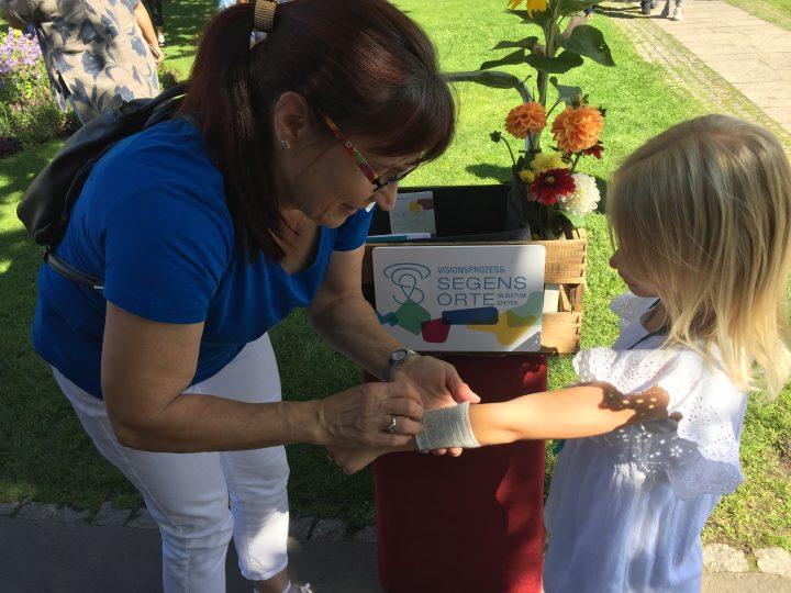 Das Bild zeigt eine Fra, die einem Kind ein Tatoo auf den Arm klebt