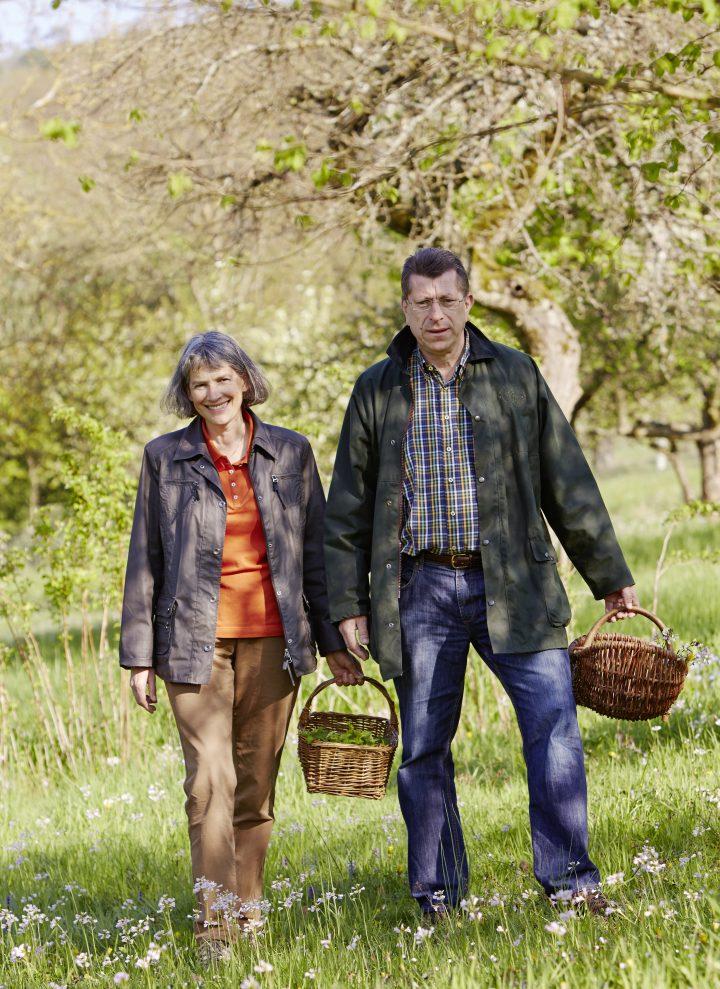 Das Bild zeigt Ursula und Johannes Schauer mit Körben in der Hand auf einer Wiese