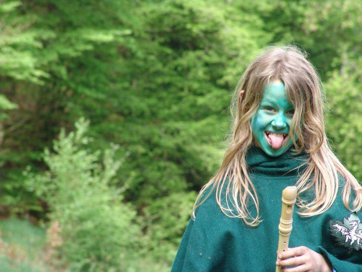Das Bild zeigt ein grün angemaltes Kind, das die Zunge raustreckt und eine Flöte in der Hand hat
