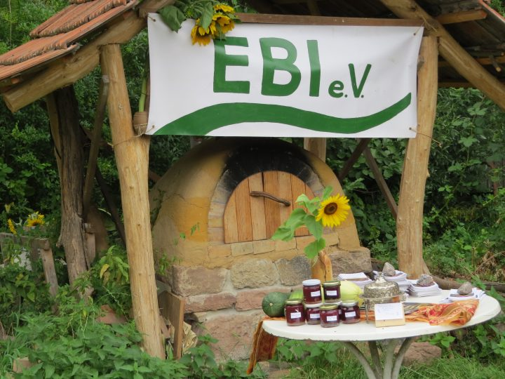 Das Bild zeigt einen kleinen Tisch mit selbstgemachten Produkten vor einem Holzofen