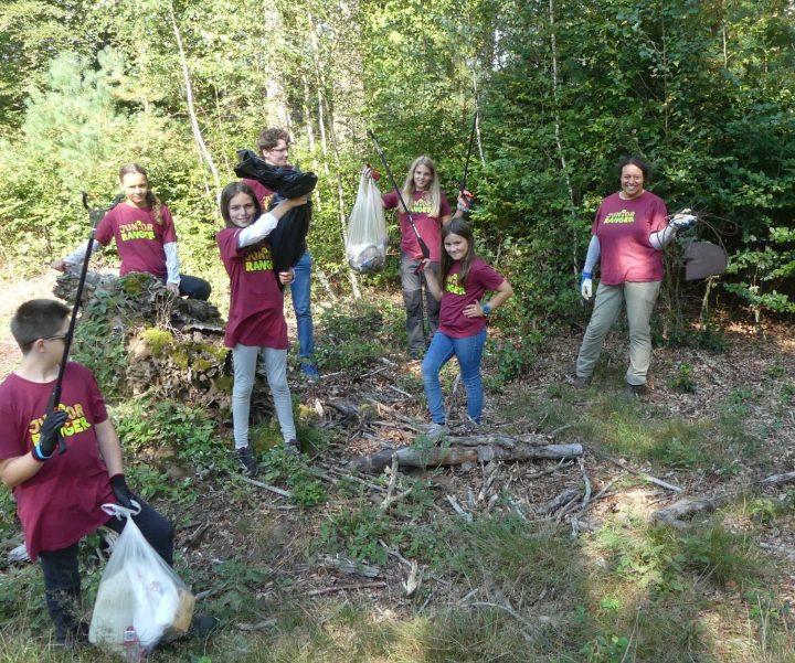 Das Bild zeigt eine Gruppe Junio Ranger:innen, die stolz ihre vollen Müllsäcke zeigen