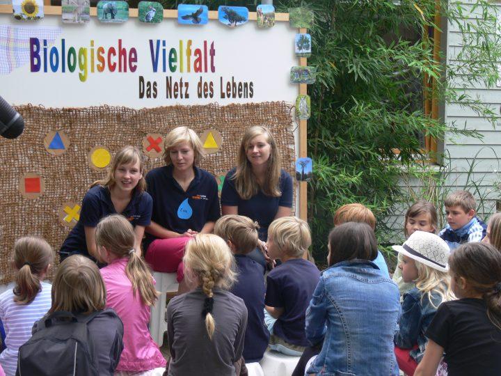 Das Bild zeigt eine Gruppe von Kindern, die aufmerksam einem Dreierteam von Erwachsenen zuhören